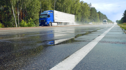 View from ground of traffic on wet road, highway with mist splash after rain with green trees on a roadside on background. Trucks are passing by camera in perspective