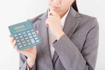 電卓を見て悩む女性、電子計算機、予算、コスト
