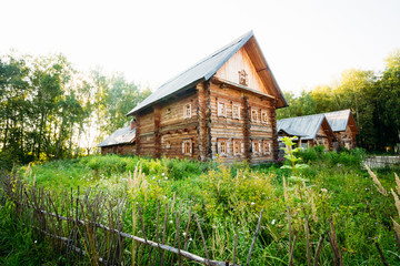 Classic Russian log house from among the green grass