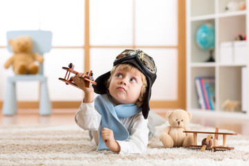 Child boy playing with toy airplane and dreaming of becoming a pilot