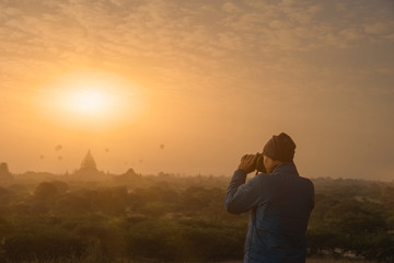 male traveler photographing temples and balloons at Bagan Myanm