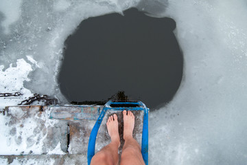 men is legs on the ice near the ice hole