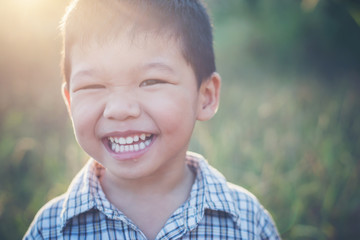 Close up of cute asian boy playing and smiling outdoors. Cute li