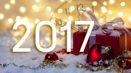 Red gift box on snow with bokeh background with 2017 year