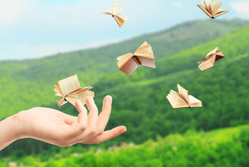 Female hand and flying books on landscape background