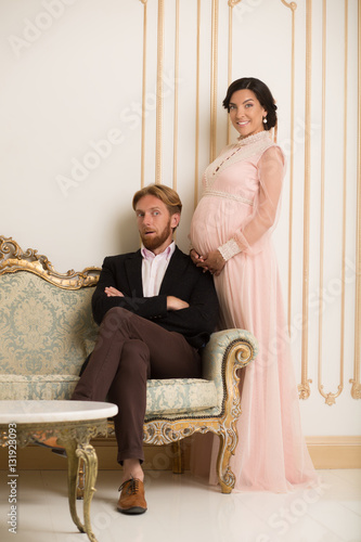 11d132b5c8 Handsome rich man sitting on sofa and looking at his pregnant wife. Happy  royal couple expecting baby soon. Royalty concept.