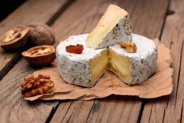 Camembert with nuts,raisins and on rustic wooden background.selective focus