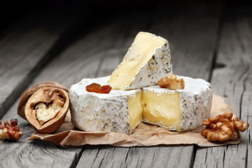 Creamy Camembert with nuts,raisins and on rustic wooden background.selective focus