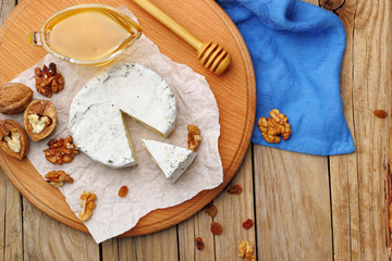 Camembert and brie cheese on wooden background with nuts spices and honey. Italian food. top view