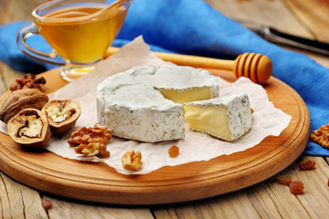Camembert and brie cheese on wooden background with nuts spices and honey. Italian food.