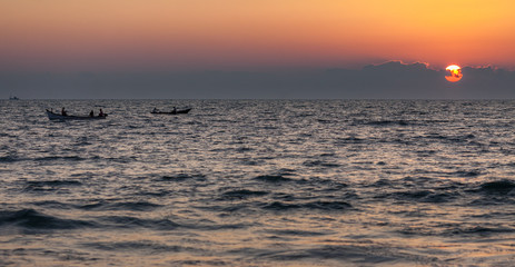 Fishing boats on waves of the Indian Ocean, against the background of the sunset. The sun hides in clouds.