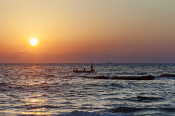 Fishermen come back from fishing with fish. The boat shakes on waves of the Indian Ocean on a sunset.