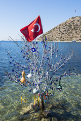Turkish flag flying above tree decorated with traditional good luck amulets in Bodrum, Turkey