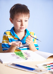 Child painting with aquarelles.