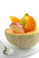 Sliced cantelope with apple, banana, and orange