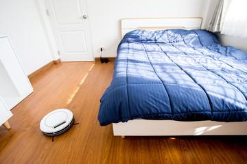 Robotic vacuum cleaner in bedroom.