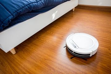 Robotic vacuum cleaner in bedroom.