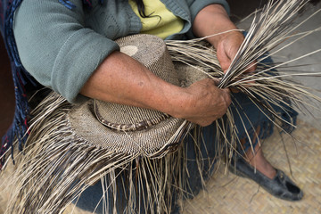 hand weaving a straw hat in San Bartolome Ecuador