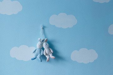 Sweet and romantic couple of lovers rabbits toy against the wall of clouds and sky