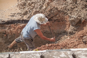 worker male dig a hole to fix  water leak at  large  on the road