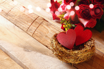 Couple of red hearts in the nest on wooden table