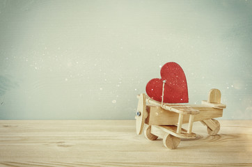Wooden plane with heart on the table