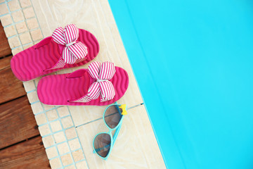 Sunglasses and flip flops by swimming pool