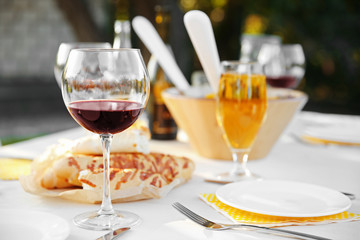 Plate, fork and glass of red wine on table, close up view