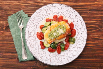 Tasty baked chicken breasts which basil pesto sauce, tomatoes, and cheese. Healthy eating concept.