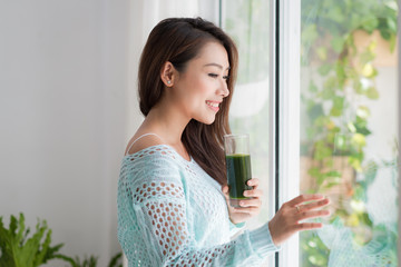 Smiling young asian woman drinking green fresh vegetable juice o