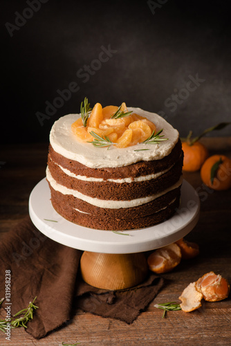 The chocolate cake with clementines and rosemary on cakestand wooden ...