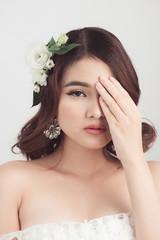 Beautiful asian woman bride on grey background. Closeup portrait