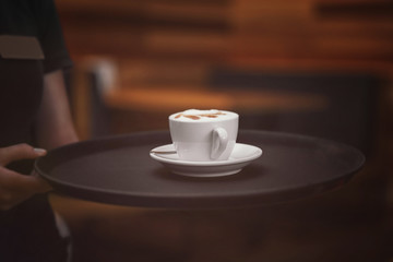Cup of tasty cappuccino on waiter tray