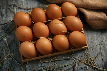 Raw eggs in box on wooden background