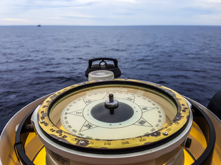 Compass aboard large ship on a blue summer sea ocean day