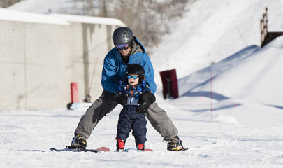 Toddler Learns to Ski with Dad. Safely Dressed with Helmet, Sunglasses, & Harness