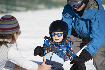 Toddler Learns to Ski with Dad While Mom Watches. Dressed Safely with Helmet, Sunglasses, & Harness.