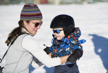 Toddler Learns to Ski at a Colorado Resort With Mom. Dressed Safely with Helmet, Sunglasses & Harness