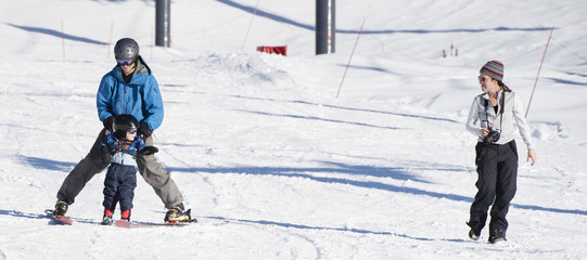 Toddler Learns to Ski with Dad While Watches & Takes Photos. Safely Dressed with Helmet, Sunglasses & Harness