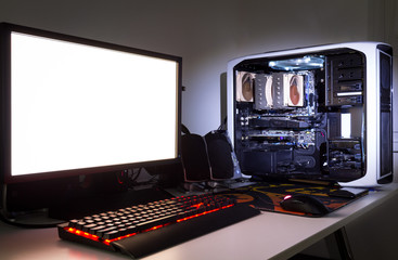Custom built gaming computer with white screen, keyboard, mouse, desktop, components, hardware, gaming chair under low light. Selective focus.