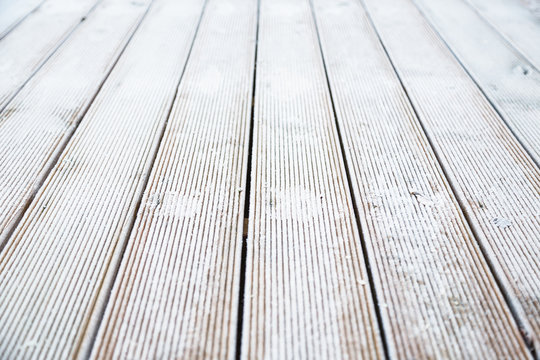Ice on decking on a frosty cold winter morning, making the wooden patio decking slippery.
