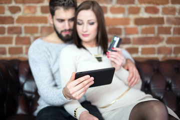 Young caucasian couple online shopping by tablet at wall