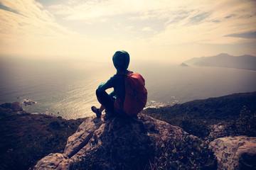 successful hiker on seaside mountain peak rock