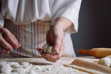 Front view of woman's hands making dough for meat dumplings.