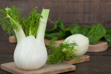 Fresh fennel and spinach on wooden boards