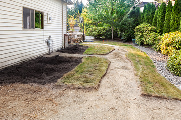 Fotobehang - Old landscaping and concrete removed, new path and patio areas cut out ready for placing stone pavers