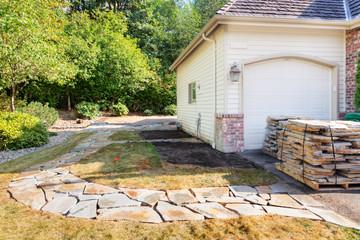 Fotobehang - Stones laid into path cutout as far as edge of patio area