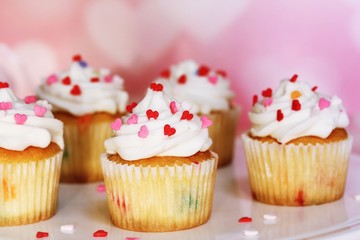 Homemade Valentine cupcakes topped with heart shaped sprinkles on Pink background,selective focus