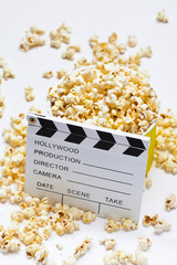 Popcorn with clapperboard on a white