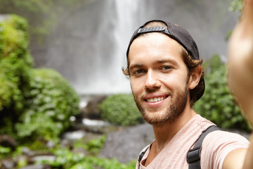 Self-portrait of happy hiker in baseball cap taking selfie via social networking app while standing against waterfall in green exotic woods. Young tourist trekking in rainforest during his holidays